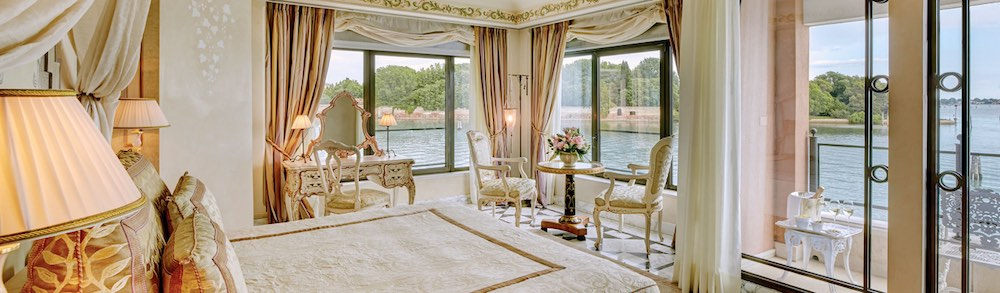 Bedroom with floor to ceiling windows and 180 degree views in the 970 square foot Palladio Signature Suite at the Belmond Cipriani Hotel in VeniceItaly