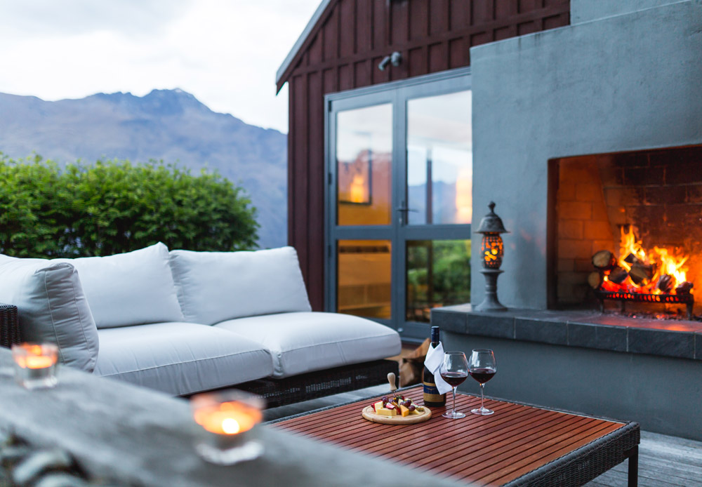 Have cheese and wine by an outdoor fire at Azur Lodge, Queenstown