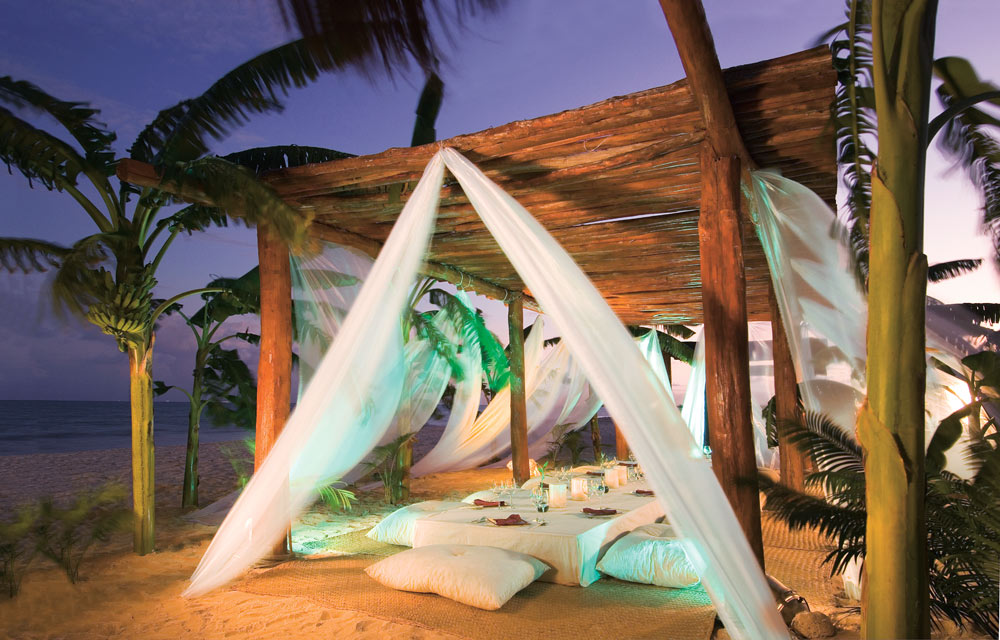 White drapery low table and pillow seating on the beach at Secrets Capri Riviera Cancun in Playa Del CarmenMexico