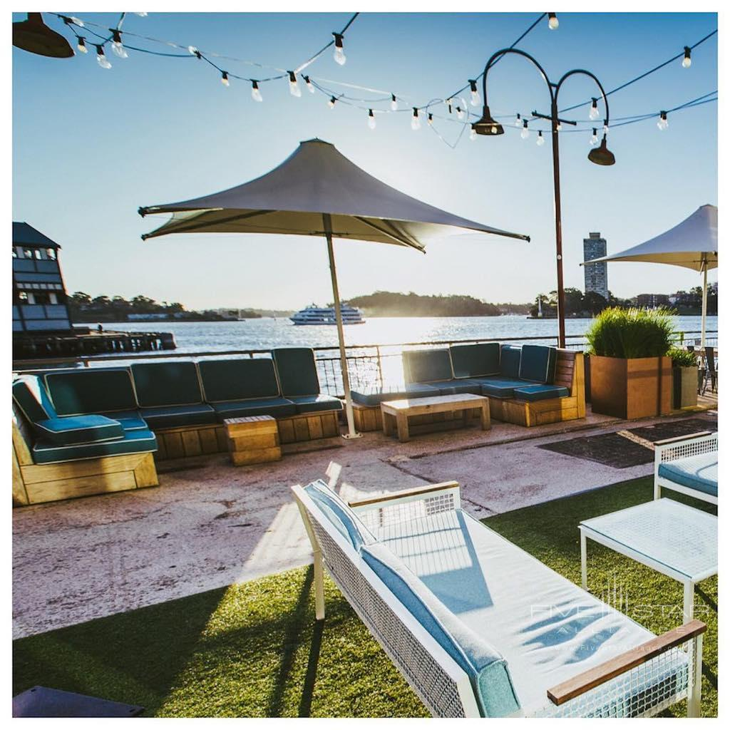 Pier umbrellas and outdoor lounges are the perfect place to watch the sunset at the Pier One Sydney Harbour Hotel