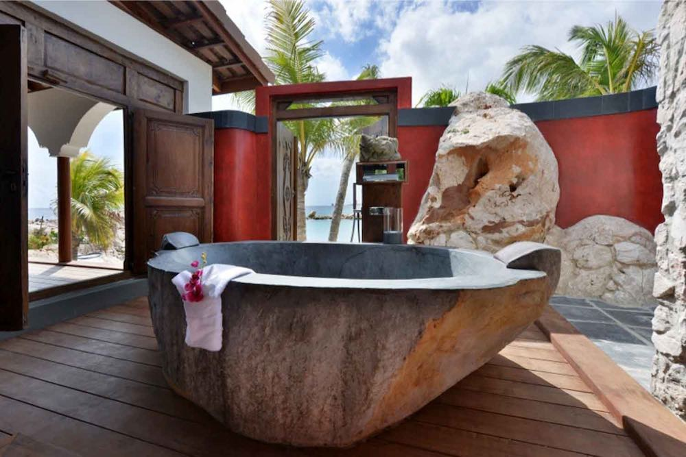 Outdoor bathroom and tub in a Superior Beachfront pool suite at the Baoase Luxury Resort in Curaçao